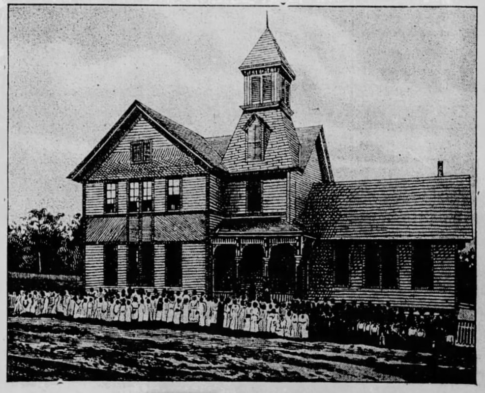Two-story wooden schoolhouse with African American children in front of it.
